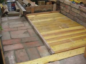 Ziegel und Holz als Boden im Gewächshaus